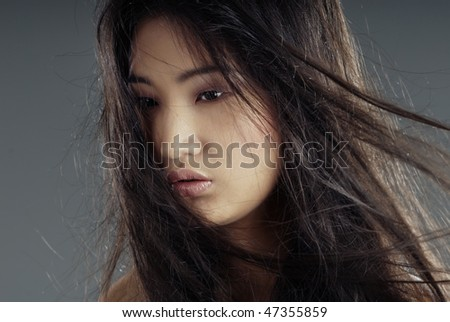 Close-up portrait of the young Asian lady with long hairs - stock photo