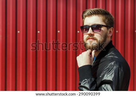 Close-up portrait of thoughtful stylish handsome bearded young man. Wearing fashionable clothes and sunglasses. Looking at the camera. In the city, on red corrugated fence background - stock photo