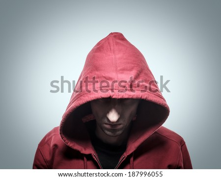 Close-up portrait of threatening gangster wearing a hood, representing the concept of danger. - stock photo