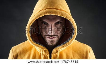 Close-up portrait of threatening man wearing a hood against black background. Danger concept. - stock photo