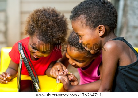 Close up portrait of three African young girls playing together on digital tablet. - stock photo