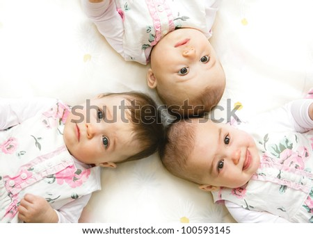 Close-up portrait of three babies lying on floor