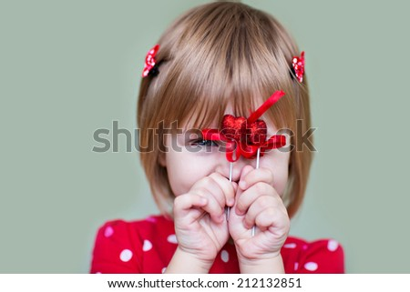 Close up portrait of three years old caucasian blond cute child girl in a red dress holding red heart symbol on a grey background. Love, Valentine's Day or charity concept. Kids and holidays. - stock photo