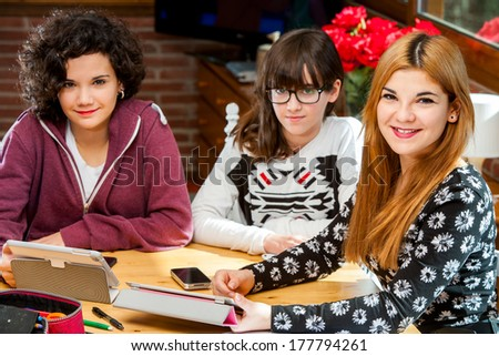 Close up portrait of threesome female students with tablets at desk.