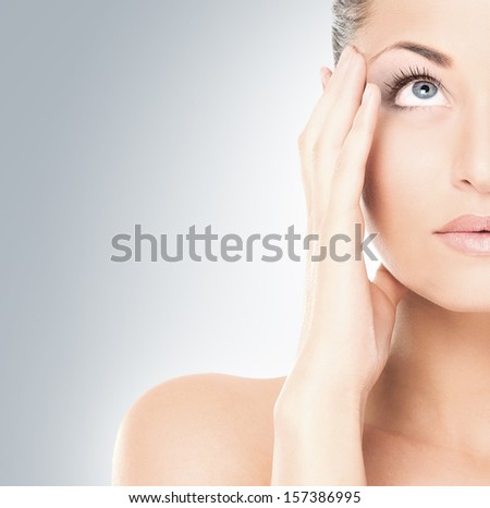 Close-up portrait of tired and upset girl over grey background - stock photo
