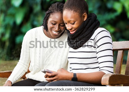 Close up portrait of two african american teenage girlfriends socializing on smart phone. Girls sitting on wooden bench in park against green background. - stock photo