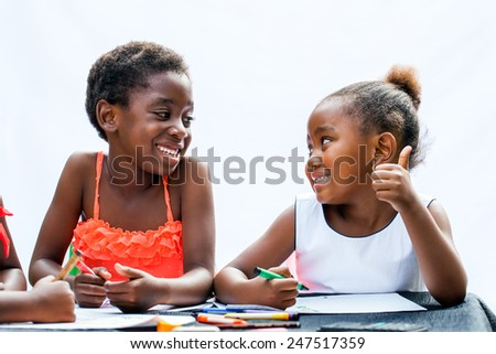 Close up portrait of two African girls with wax crayons at desk.One is showing thumbs up to friend.Isolated on light background.