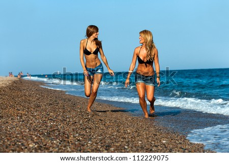 Close up portrait of two attractive female friends on beach.