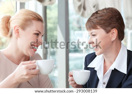 Close up portrait of two beautiful businesswomen sitting looking at each other smiling holding cups of coffee, in a restaurant during business lunch, selective focus