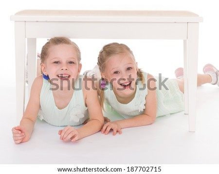 Close-up portrait of two cheerful children lying at home, happy family, love and friendship concepts