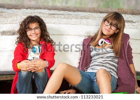 Close up portrait of two cute teenage girlfriends sitting outdoors. - stock photo