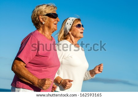 Close up portrait of two elderly women jogging outdoors. - stock photo