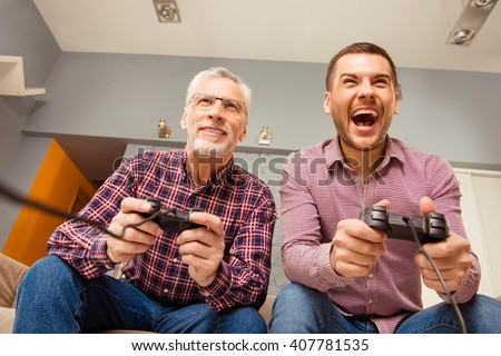 Close up portrait of two excited handsome men playing video game at home - stock photo