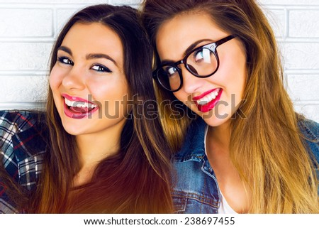 Close up portrait of two funny hipster young girl friends, having great time together smiling, have amazing long hairs and bright make up. - stock photo