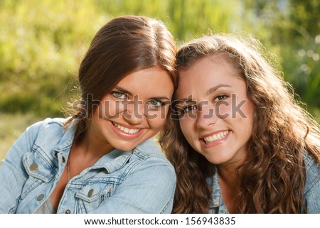 close-up portrait of two girlfriends in jeans wear outdoors sitting  smiling looking at camera