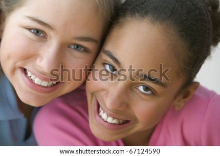 Close up portrait of two girls smiling - stock photo