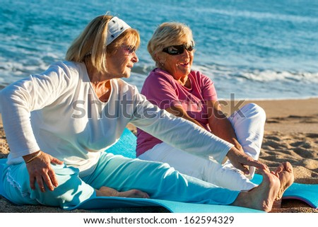 Close up portrait of two golden age women doing stretching exercises together on beach. - stock photo
