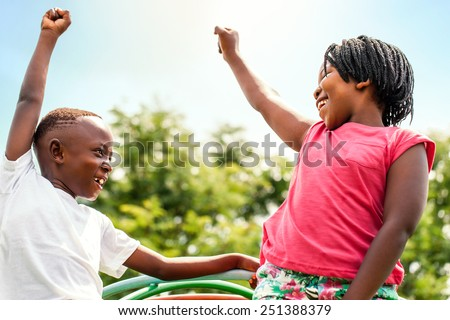 Close up portrait of two happy African kids looking at each other raising hands outdoors. - stock photo
