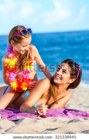 Close up portrait of two happy young women on summer holidays having fun together on beach. - stock photo