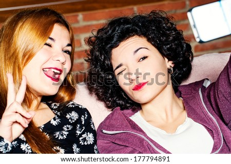 Close up portrait of two teen girls having fun with camera. - stock photo