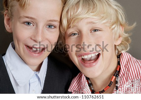 Close up portrait of two young brothers laughing with their heads together. - stock photo