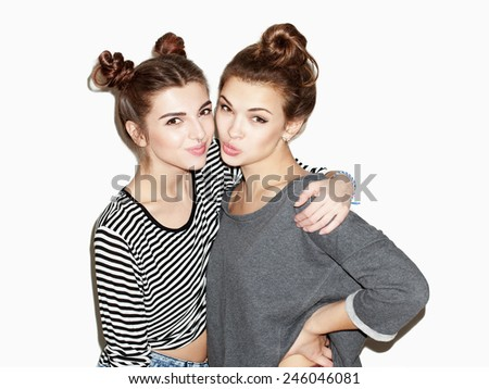 Close up portrait of two young girl having fun and hugging. - stock photo