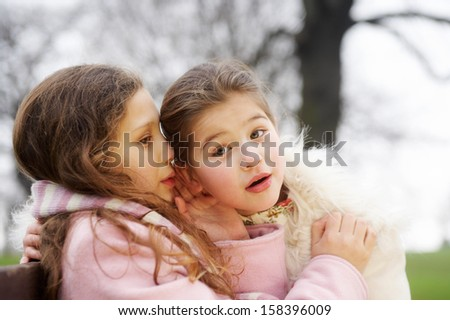 Close up portrait of two young girls children sisters sitting on a wooden bench in a park during a cold winter day, with one whispering secrets into the others ear, smiling outdoors. - stock photo