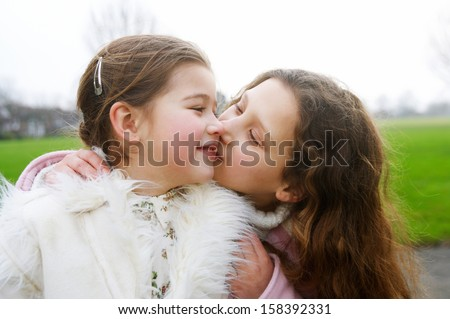 Close up portrait of two young girls children sisters together in a park during a cold winter day, with one kissing the other on the cheek, smiling and enjoying the outdoors. - stock photo