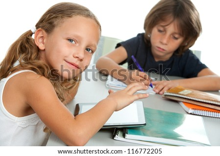 Close up portrait of two young kids doing schoolwork together at desk.Isolated. - stock photo
