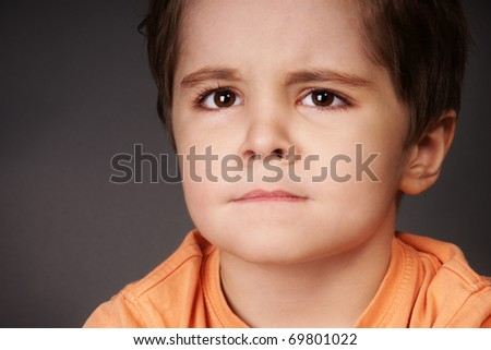 Close-up portrait of upset little boy, studio shot - stock photo