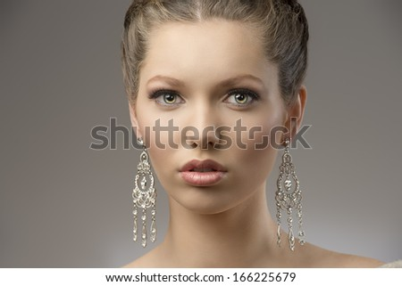 close-up portrait of very beautiful brunette girl with splendid eyes, creative hair-style  and precious earrings. looking in camera   - stock photo