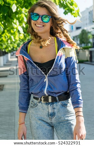 Close-up Portrait of very beautiful sports girl with mobile in hand posing on the street, positive emotions, enjoying life,sports concept, wearing aviator glasses, attractive figure, positive emotions