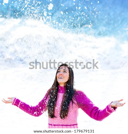 Close up Portrait of winter girl playing under snowflakes.