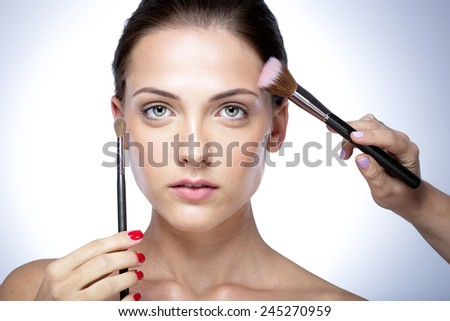 Close-up portrait of woman applying makeup on the face with brush - stock photo