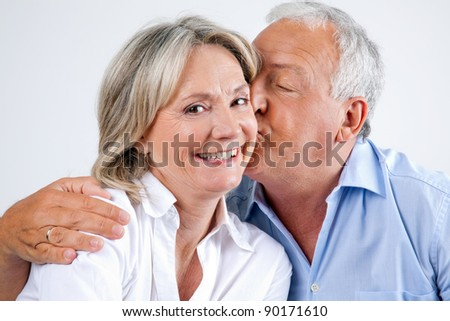 Close-up portrait of woman being affectionately kissed by her husband - stock photo