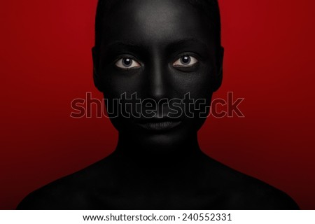 close-up portrait of woman in black paint isolated on red - stock photo