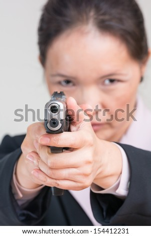 Close up portrait of woman in business suit aiming a pistol at you - stock photo
