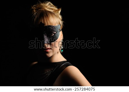 Close up portrait of woman in mysterious mask over black background - stock photo