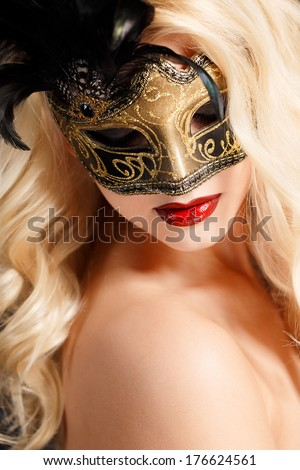 Close up portrait of woman in venetian mask..Carnival mask Close-up female portrait.Blue eyes. Dark background - stock photo