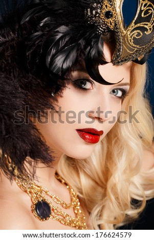 Close up portrait of woman in venetian mask..Carnival mask Close-up female portrait.Blue eyes. Dark background