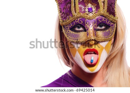 close up portrait of woman in violet mask with blue pill on tongue - stock photo