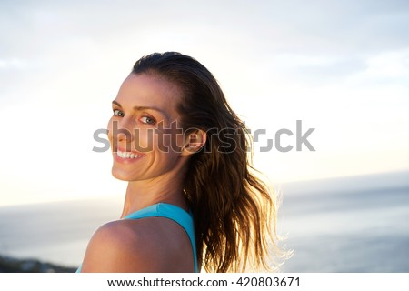 Close up portrait of woman looking over shoulder with sea in background