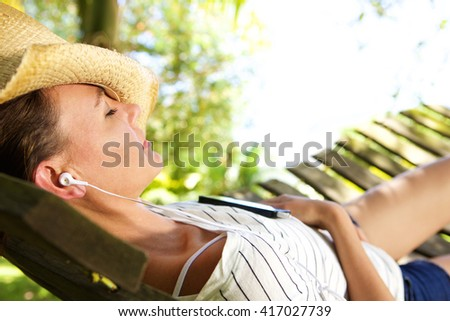 Close up portrait of woman lying down on hammock listening to music with cell phone - stock photo