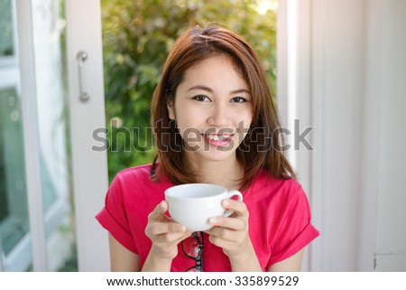 Close up portrait of woman smiling and drinking coffee , Selective focus on women eyes.
