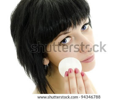 Close-up portrait of woman with cotton swab cleaning her face. Isolated on white.