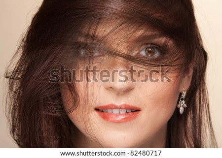 Close-up portrait of woman with her beautiful hairs flying on wind hiding eyes - stock photo