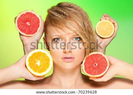 Close up portrait of woman with many juicy citrus fruit in four hands - stock photo