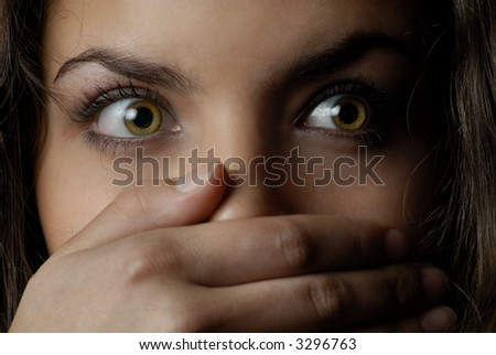 Close-up portrait of woman with mouth closed by the hand - stock photo