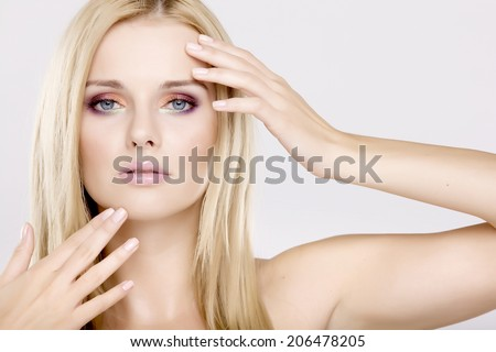 Close up portrait of young adult pretty woman with beautiful blond hairs and multicolor makeup isolated on white background - stock photo