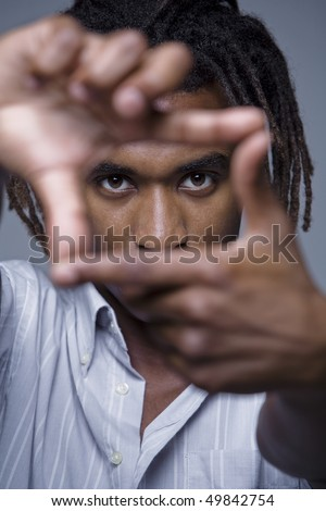 Close-up portrait of young African American man looking through framed hands, studio shot